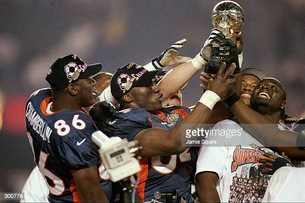 Shannon Sharpe and teammates hold up the Lombardi Trophy after defeating the Green Bay Packers in Super Bowl XXXII at Qualcomm Stadium in San Diego...