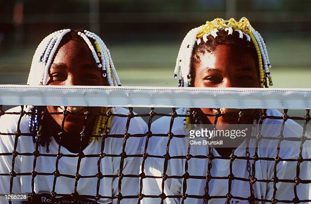 Teenage tennis sisters from America Venus and Serena Williams take time off a practise session to pose together during the Adidas International event...