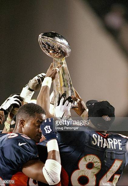 The Denver Broncos players hold up the Lombardi Trophy after defeating the Green Bay Packers in Super Bowl XXXII at Qualcomm Stadium in San Diego...