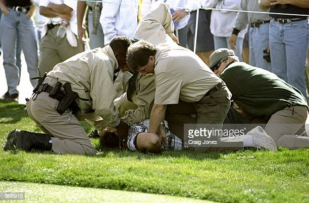 A fan is hand cuffed by police for heckling Tiger Woods and also having a concealed hand gun the during the Phoenix Open at the TPC of Scottsdale in...