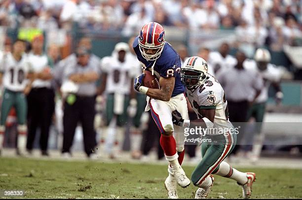 Andre Reed of the Buffalo Bills being tackled by Patrick Surtain after catching the ball during the AFC Wild Card Game against the Miami Dolphins at...