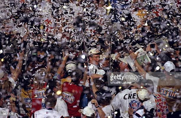 Confetti rains down as quarterback John Elway of the Denver Broncos is mobbed by teammates and fans after defeating the Atlanta Falcons to win Super...