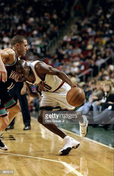 Gary Payton of the Seattle Supersonics dribbles the ball during the game against the Vancover Grizzlies at the Key Arena in Seattle Washington The...