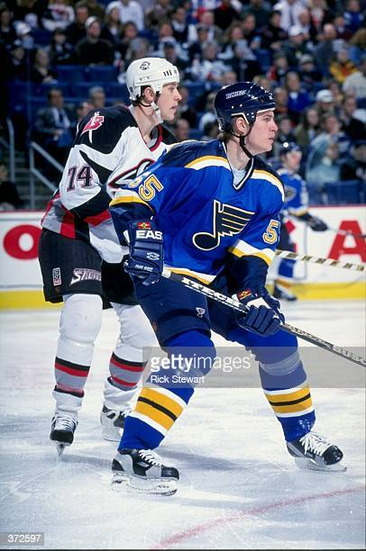 Jochen Hecht of the St. Louis Blues waits for the puck as Jay Makee guards him during the game against the Buffalo Sabres at the Marine Midland Arena...