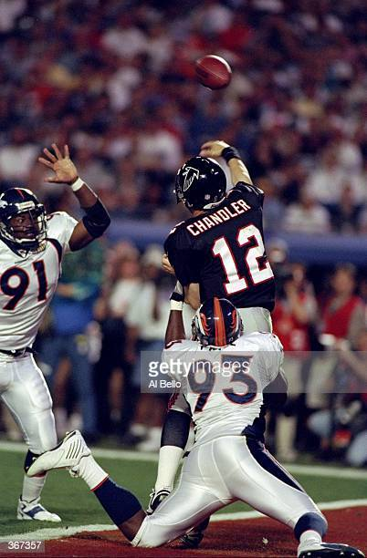 Quarterback Chris Chandler of the Atlanta Falcons throws an interception as he is tackled by Trevor Pryce and Alfred Williams of the Denver Broncos...