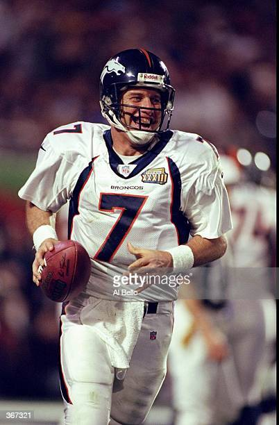 Quarterback John Elway of the Denver Broncos smiles as he celebrates after scoring a touchdown during the fourth quarter of Super Bowl XXXIII against...