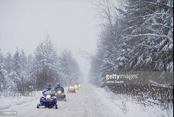 Snowmobilers drive with their lights on during the World Championship Snowmobile Derby in Eagle River Wisconsin Mandatory Credit Jamie Squire...