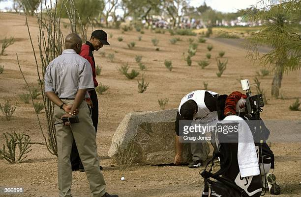 Tiger Woods with his caddie Fluff look at a boulder which is in the way during the Phoenix Open at the TPC of Scottsdale in Scottsdale Arizona