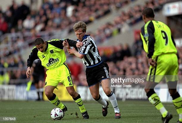 Curtis Woodhouse of Sheffield United is tackled by Warren Barton of Newcastle during the FA Cup 4th Round match played at St James's Park in...