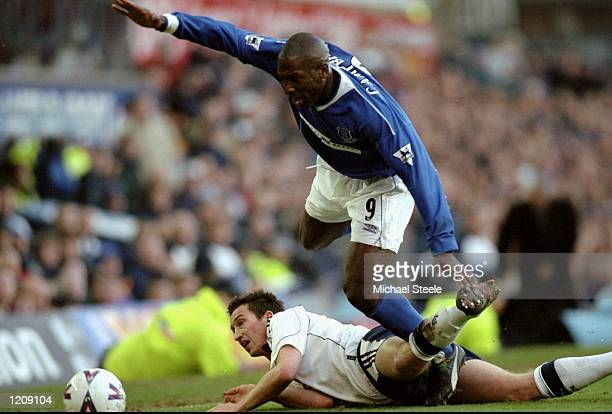 Kevin Campbell of Everton jumps over the sprawling Justin Edinburgh of Tottenham Hotspur during the FA Carling Premier League match played at...