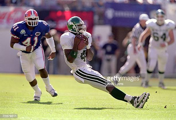 Plaxico Burress of the Michigan State Spartans slids to the ground with the ball during the Citrus Bowl Game against the Florida Gators at the Citrus...