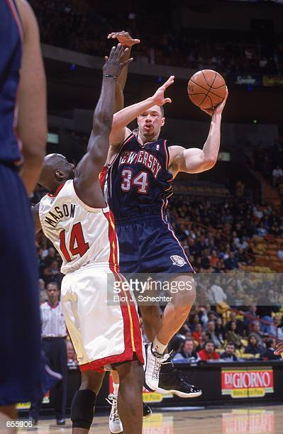 Aaron Williams of the New Jersey Nets leaps up to pass the ball against Anthony Mason of the Miami Heat during the game at the American Airlines...