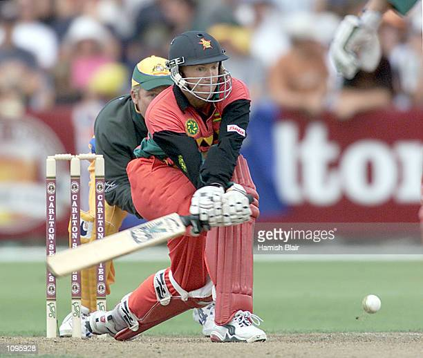 Andrew Flower of Zimbabwe reverse sweeps for four on his way to a half century during the Carlton Series One Day International between Australia and...