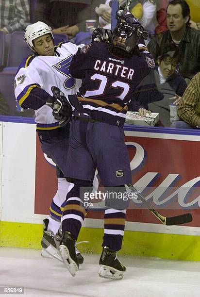 Bryce Salvador of the St Louis Blues is hit by Anson Carter of the Edmonton Oilers at the Savvis Center in St Louis Missouri The StLouis Blues beat...