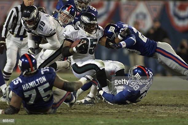 Chris Warren of the Philadelphia Eagles is tackled by a group of New York Giants during the NFC Divisional playoff game at Giants Stadium in East...