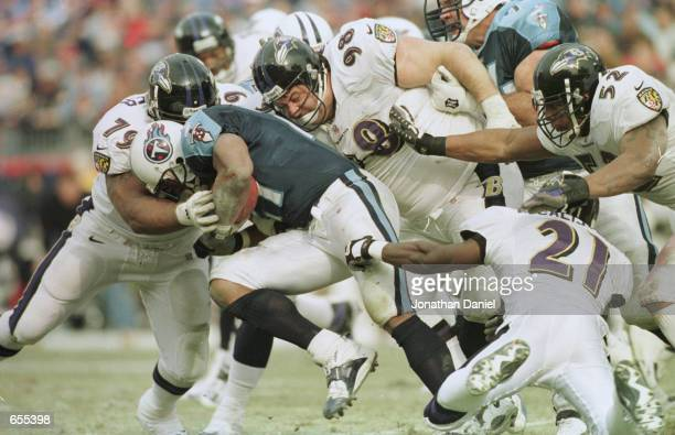 Eddie George of the Tennessee Titans is stopped by the Baltimore Ravens defense lead by Larry Webster and Tony Siragusa during the AFC Playoff game...