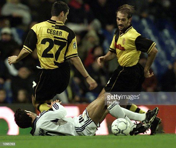 Figo of Madrid is brought down by Lanna and Cesar of Zaragoza during the Real Madrid v Real Zaragoza Primera Liga match played at the Santiago...