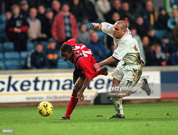 Jermain Defoe of Bournemouth is held back bt Millwall's Robbie Ryan during the Nationwide Division Two match between Millwall and Bournemouth at the...