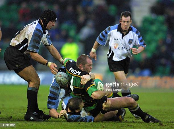 Jon Phillips of Northampton Saints is brought down by John Tait and Jon Humphreys of Cardiff during the Heineken Cup match at Franklin's Gardens in...