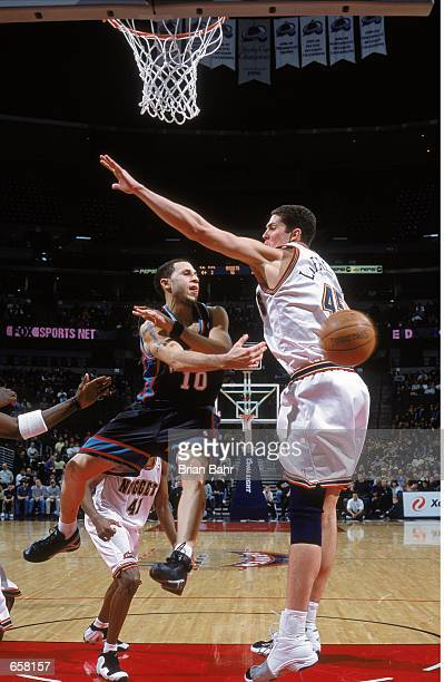 Mike Bibby of the Vancouver Grizzlies jumps as he passes the ball around Raef La Frentz of the Denver Nuggets at the Pepsi Center in Denver Colorado...
