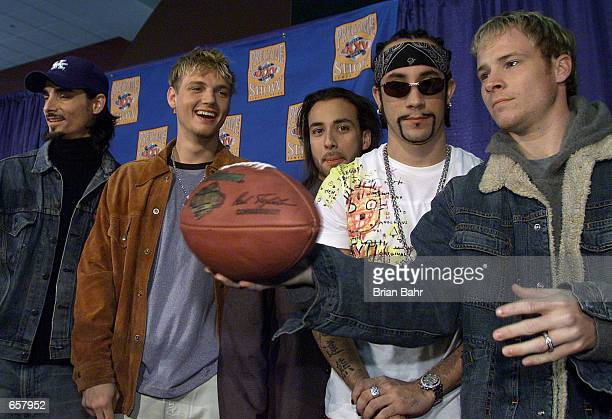 Pop group The Backstreet Boys play with a football during the press conference for the Super Bowl pregame show at Raymond James stadium in Tampa...