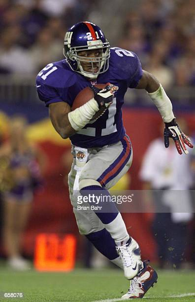 Running back Tiki Barber of the New York Giants carries the football during Super Bowl XXXV against the Baltimore Ravens at Raymond James Stadium in...