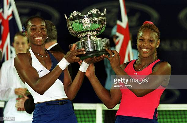 Venus and Serena Williams of the USA hold the winners trophy after defeating Lindsay Davenport and Corina Morariu of the USA, in the Final of the...