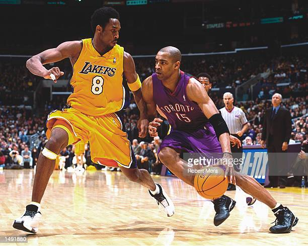 Vince Carter of the Toronto Raptors drives to the basket against Kobe Bryant of the Los Angeles Lakers during an NBA Game at the Staples Center in...