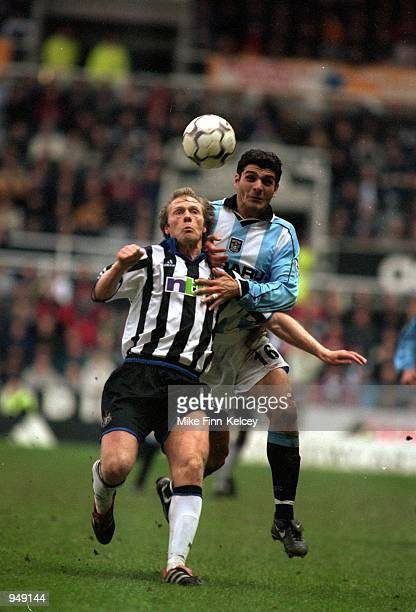 Warren Barton of Newcastle United clears the ball despite the challenge from John Aloisi of Coventry City during the FA Carling Premiership match...