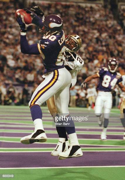 Wide receiver Cris Carter of the Minnesota Vikings pulls down a catch for a touchdown over the reach of cornerback Kevin Mathis of the New Orleans...