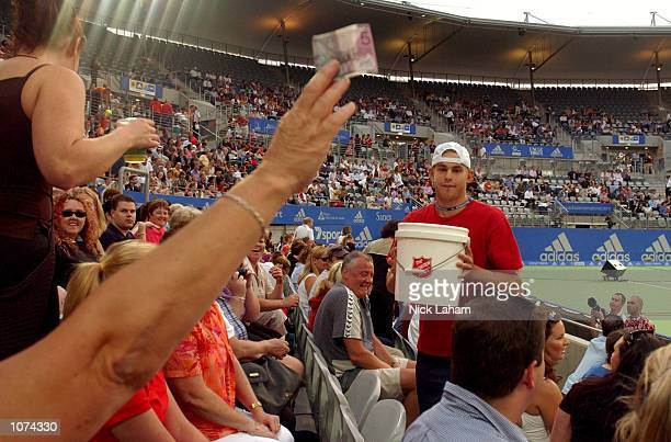 Andy Roddick of the United States collects money for the Salvation Army appeal to aid the Australian victims of the Christmas bushfires during day 4...