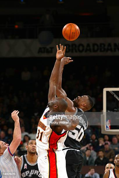 David Robinson of the San Antonio Spurs and Adonal Foyle of the Golden State Warriors tips off to start the game at The Arena in Oakland California...