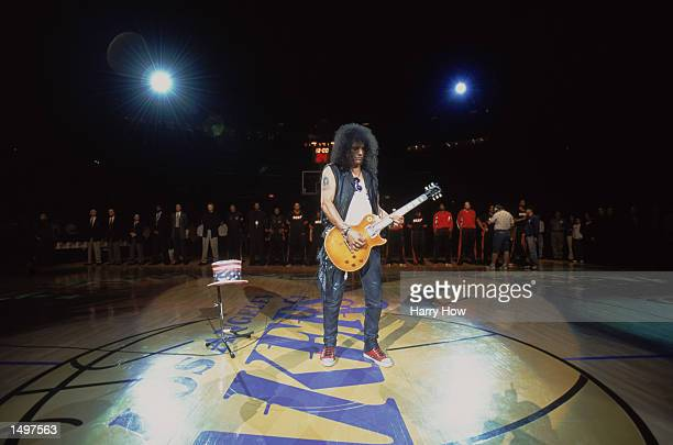 Former Guns ''n Roses guitarist Slash plays for the the NBA fans prior to the the game between the Miami Heat and the Los Angeles Lakers at the...