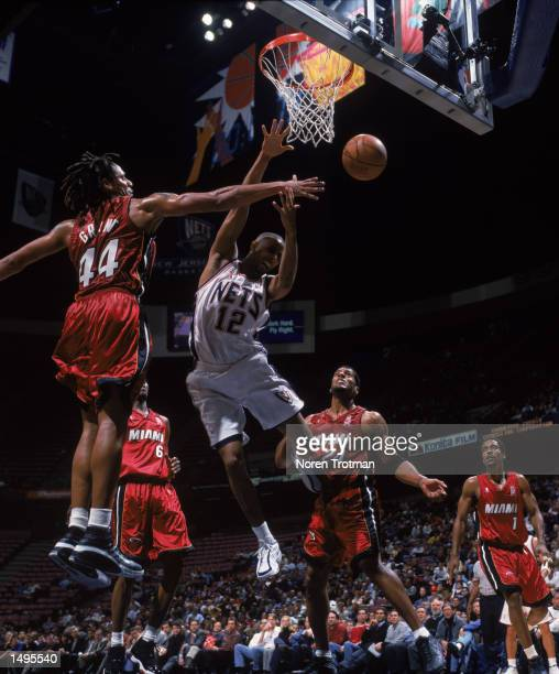 Forward Brian Grant of the Miami Heat blocks guard Lucious Harris of the New Jersey Nets during the NBA game at Continental Airlines Arena in East...