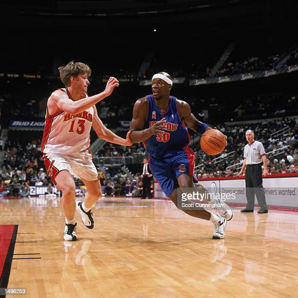 Forward Clifford Robinson of the Detroit Pistons drives past forward Hanno Mottola of the Atlanta Hawks during the NBA game at Philips Arena in...