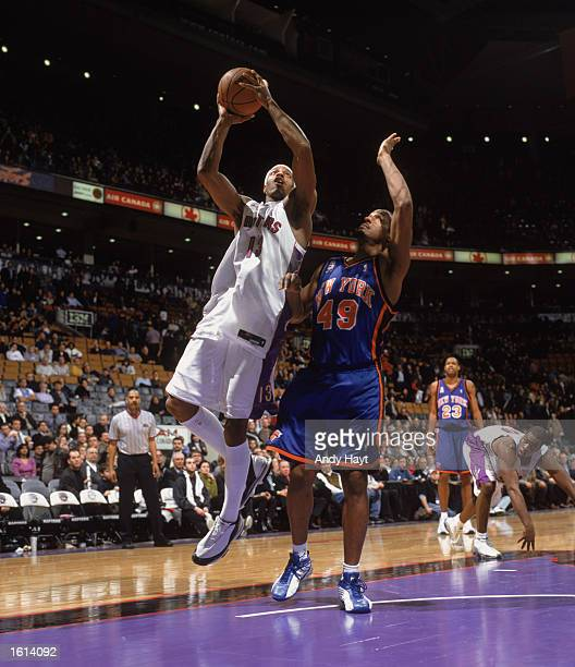 Forward Jerome Williams of the Toronto Raptors shoots over guard Shandon Anderson of the New York Knicks during the NBA game at Air Canada Centre in...