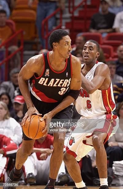 Forward Scottie Pippen of the Portland Trail Blazers passes around guard Eddie Jones of the Miami Heat during the NBA game at American Airlines Arena...