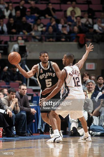 Guard Charles Smith of the San Antonio Spurs passes around guard Lucious Harris of the New Jersey Nets during the NBA game at Continental Airlines...