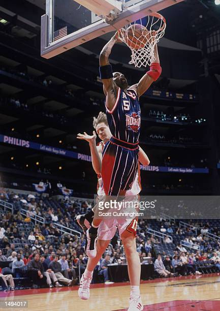 Guard Cuttino Mobley of the Houston Rockets dunks the ball as forward Hanno Mottola of the Atlanta Hawks attempts to block during the NBA game at the...