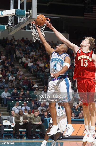 Guard David Wesley of the Charlotte Hornets shoots past forward Hanno Mottola of the Atlanta Hawks during the NBA game at the Charlotte Colesium in...
