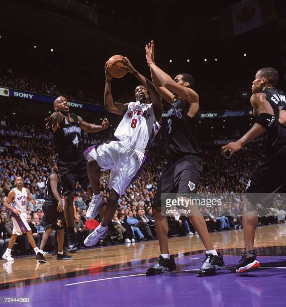 Guard Jermaine Jackson of the Toronto Raptors shoots the ball as two Minnesota Timberwolves center Loren Woods and forward Chauncey Billups play...