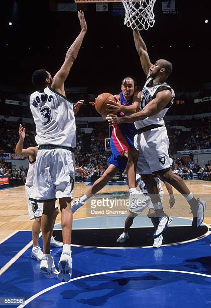 Guard Jon Barry of the Detroit Pistons drives between center Loren Woods and forward Gary Trent of the Minnesota Timberwolves during the NBA game at...