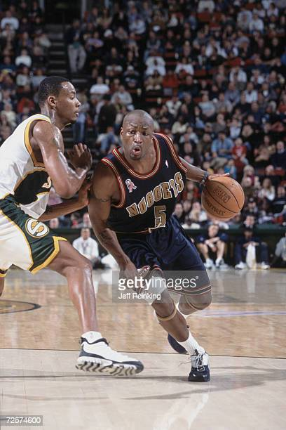 Guard Voshon Lenard of the Seattle SuperSonics dribbles around guard Rashard Lewis of the Seattle SuperSonics during the NBA game at the Key Arena in...