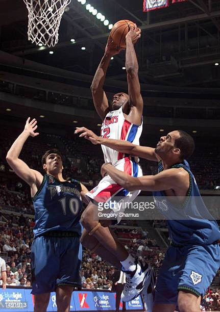 Jerry Stackhouse of the Detroit Pistons goes to the basket between Wally Szczerbiak and Loren Woods of the Minnesota Timberwolves at The Palace of...