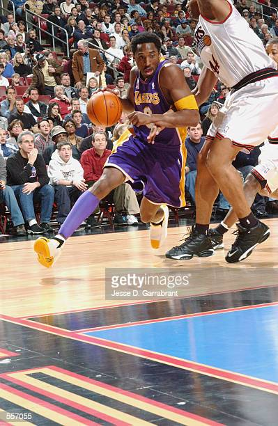 Kobe Bryant of the Los Angeles Lakers drives around Derrick Coleman of the Philadelphia 76ers during their game at the First Union Arena in...