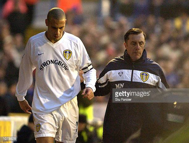Leeds Physio walks back with Rio Ferdinand as he limps of injuried during the AXA FA Cup Third Round match between Cardiff City and Leeds United at...