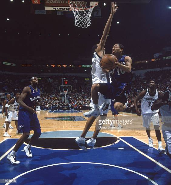 Point guard Tyronn Lue of the Washington Wizards jumps past center Loren Woods of the Minnesota Timberwolves during the NBA game at the Target Center...