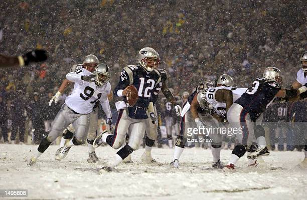 Quarterback Tom Brady of the New England Patriots runs in for a touchdown over the defense of Regan Upshaw the Oakland Raiders during the AFC playoff...