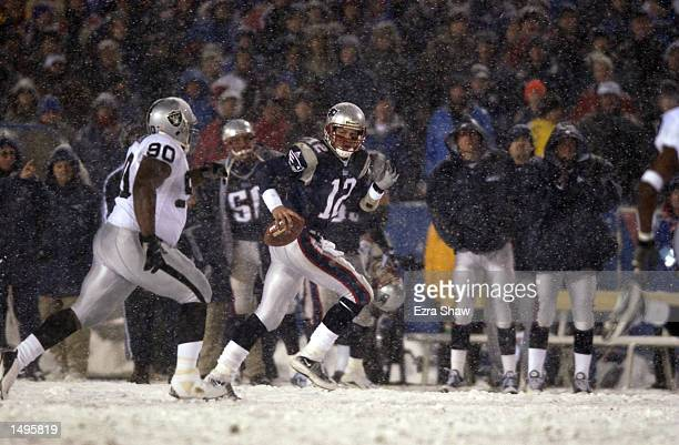 Quarterback Tom Brady of the New England Patriots scrambles against the Grandy Jackson of the the Oakland Raiders during the AFC playoff game at...