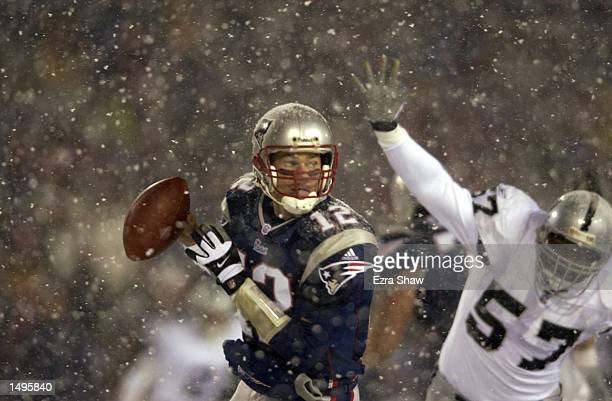 Quarterback Tom Brady of the New England Patriots scrambles against the defense of Rod Coleman of the Oakland Raiders during the AFC playoff game at...